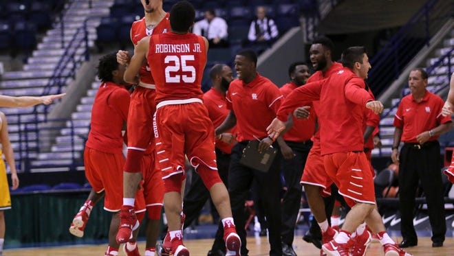Rob Gray and Galen Robinson Jr., along with the rest of the Houston men's basketball team, celebrate winning against Vermont in the final seconds of the Gulf Coast Showcase championship game, 72-71.