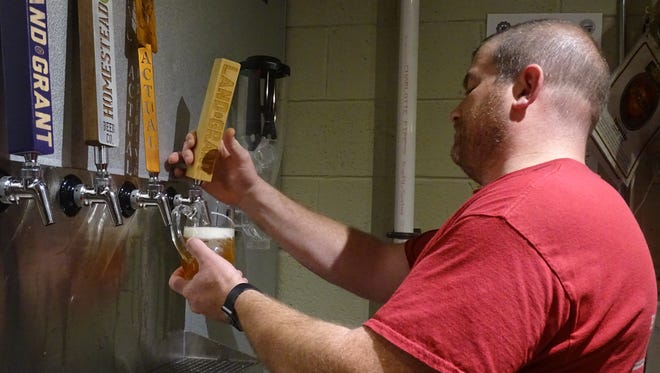 Owner Chris Stone pours one of his favorite beers on draft into a mug.