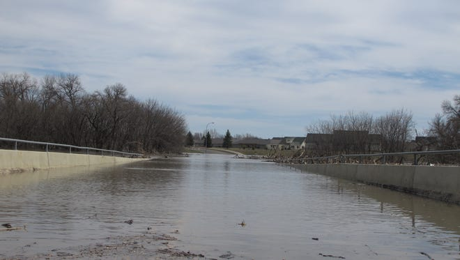 The Red River flows over the 12th Street North bridge, shown looking from Fargo, N.D., into Moorhead in April of 2013.