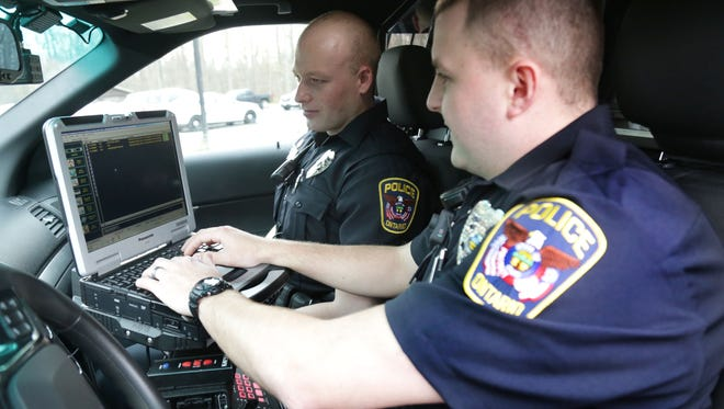 Ontario police officers Casey Bly and David Rowland demostrates the computer filing system inside on the department's cruisers.