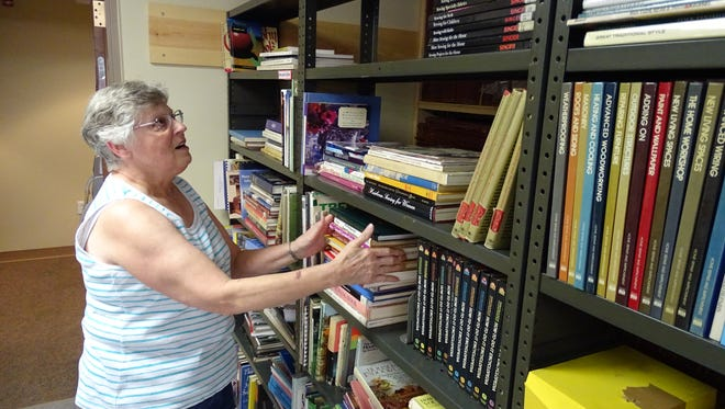 Sarah Gebhardt arranges books for last year's Friends of the Bucyrus Public Library book sale.