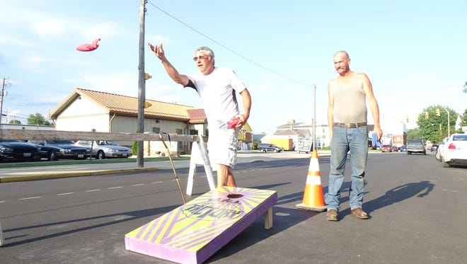 Andy Thoroughman, left, and Roger Clark, both of Bucyrus, toss corn hole in front of SK8 Factory on Mansfield Avenue in Bucyrus as part of the National Night Out festivities, last year.