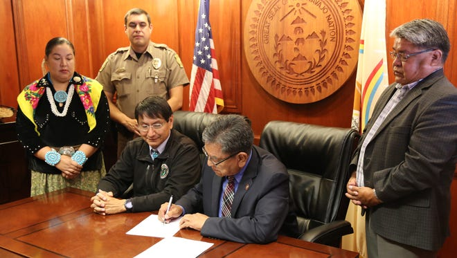 Navajo Nation President Russell Begaye, center, signs a resolution on Monday in Window Rock, Ariz. to establish human trafficking on tribal land as a criminal offense.