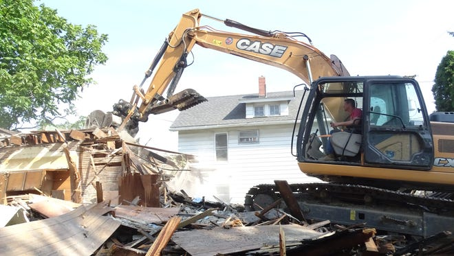 Justin Beck, owner of GMC Excavation out of Galion, tears down the multi-family home at 407 and 409 Sheckler Ave. in Bucyrus early Wednesday.