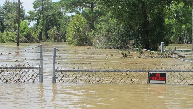 FILE - In this Aug. 31, 2017 file photo, a barbed-wire fence encircles the Highlands Acid Pit that was flooded by water from the nearby San Jacinto River as a result from Harvey in Highlands, Texas.  Floodwaters have inundated at least five highly contaminated toxic waste sites near Houston, raising concerns that the pollution there might spread.