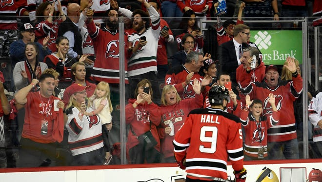 Devils fans celebrate after New Jersey Devils left wing Taylor Hall (9) first goal in the second period during the home opener against the Anaheim Ducks at the Prudential Center in Newark, N.J. on Tuesday, October 18, 2016.