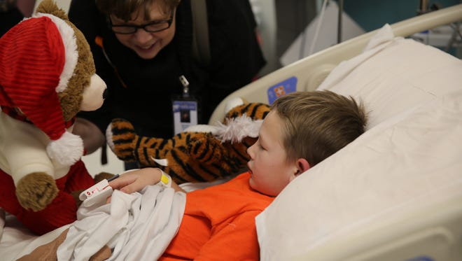 Danielle Young gives patient Cooper Hubbs, 5, a teddy bear Wednesday at the San Juan Regional Medical Center in Farmington.