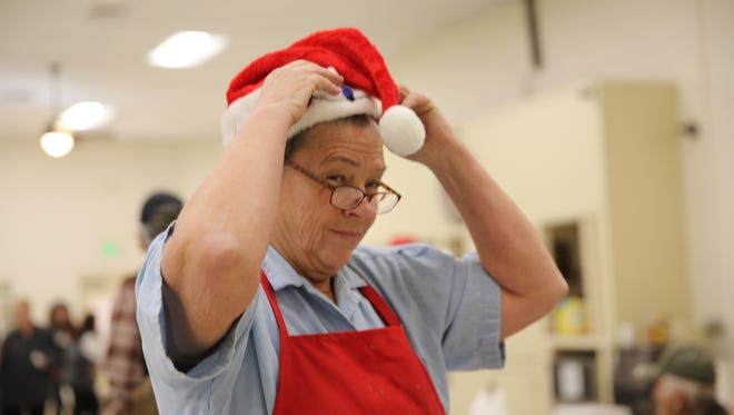Susan Rarick puts on a Christmas hat, Monday, Dec. 25, 2017, while volunteering at the Aztec community Christmas dinner.
