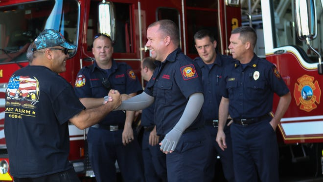 Lt. Manny Vazquez shakes hands with fellow firefighter Brad Speakman a year after the deadly Canby Park fire that killed three of their fellow firefighters.