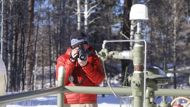 Pete Dronkers, southwest circuit rider for Earthworks, checks for emissions at a gas well next to Navajo Route 13 near Buffalo Pass in Arizona on Jan. 11.