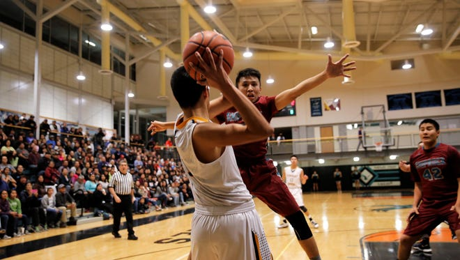 Shiprock's Lennard Hoskie, No. 3 in maroon, looks to deflect an inbound pass by Navajo Prep's Lance Morris, No. 5 in white, during the District 1-4A opener on Thursday, Jan. 25 in Farmington.
