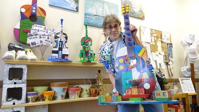 Lou Anne Michel holds one of her many artistic creations at her studio in Ashland.