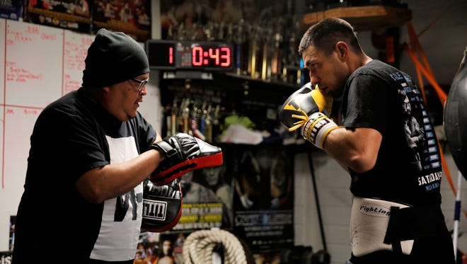 Aztec's Joe Martinez, seen here working with trainer Lorenzo Whitey, left, Wednesday at his home in Aztec, beat Denver's Corey Alarcon via second-round knockout on Saturday at the Sky Ute Casino Resort Events Center in Ignacio, Colo. It was Martinez's first professional fight since May 2016.