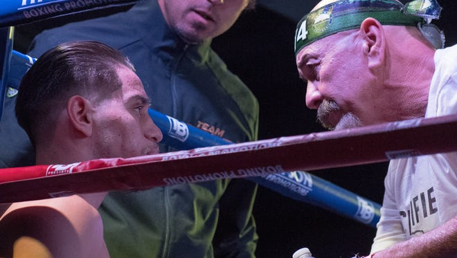 Ruben Villa IV (left) and trainer Max Garcia (right) talk things over between the third and fourth rounds of the WBO Youth Featherweight title fight Saturday night at the Salinas Storm House.