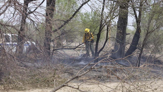 A firefighter extinguishes a hot spot from a wildfire on Monday near Navajo Route 364 and Fifth Lane in Shiprock.
