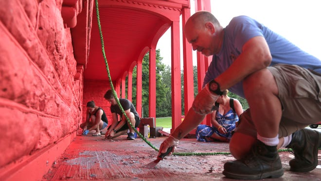 Allen Martin and several other volunteers help clean up Liberty Park by cleaning up paint on Tuesday evening.
