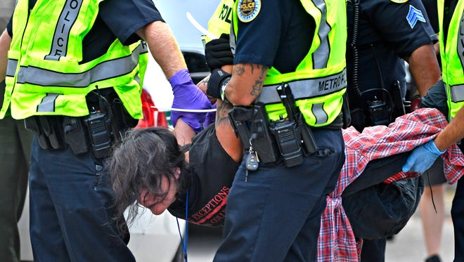 Jeannie Alexander is carried off after being arrested with other protesters blocking the entrances of Nashville-based CoreCivic, the nation's largest owner and operator of private prisons,Monday Aug. 6, 2018, in Nashville, Tenn.