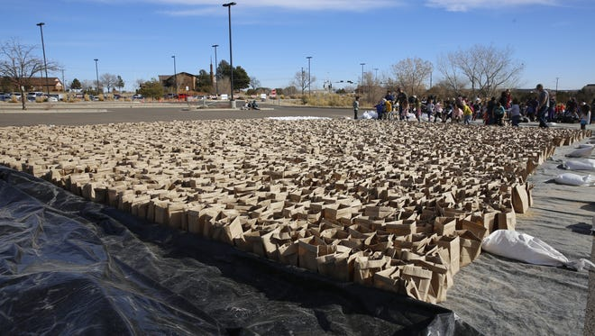 Students from Country Club Elementary School help assemble thousands of luminarias Wednesday afternoon at San Juan College for the college's annual luminarias display this weekend.