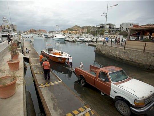 Residentes remolcan un bote para sacarlo del agua ante