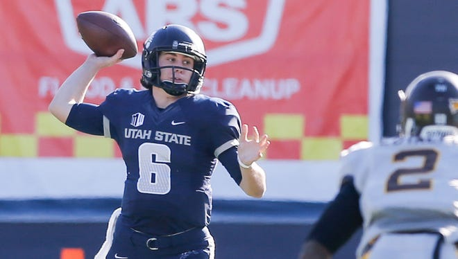 Utah State Aggies quarterback Darell Garretson passes the ball up the field against the Wyoming Cowboys during the second quarter at Romney Stadium.