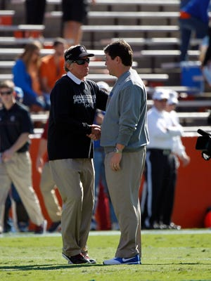 South Carolina Gamecocks head coach Steve Spurrier and Florida Gators head coach Will Muschamp talk prior to the game at Ben Hill Griffin Stadium.