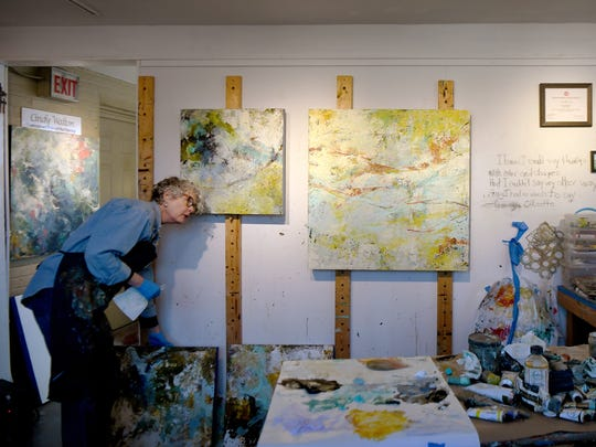 Abstract painter Cindy Walton grabs a different painting to work on at her studio in the River Arts District on Thursday, Feb. 8, 2018.