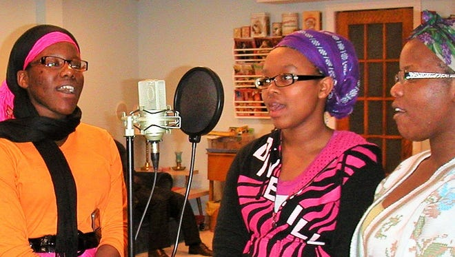 A trio of Amen Choir singers clusters around a microphone at Euphonic Studio in Mount Vernon during a recent recording session. From left are Naomi Sengiyumva, Jeanine Nyarasafari and Leya Neema, choir director.