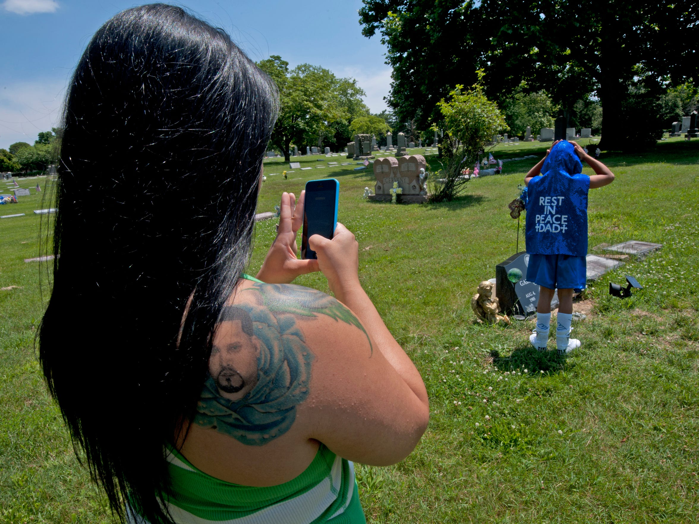 Jessica Concepcion, a tattoo of her slain husband, Gabriel Crespo on her shoulder, takes a picture of son Gabriel Gambino Crespo at his father's grave in Pennsauken before his first scheduled amateur boxing match.
