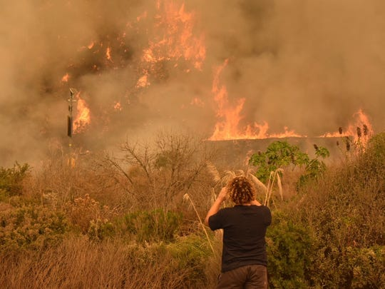 From the Pacific Coast Highway, Sara Lazarus watches flames dance on the inland side of Highway 101 Wednesday.