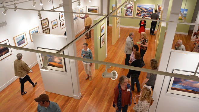 People look at an exhibit at Bush Barn Art Center.