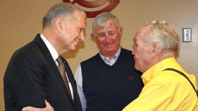 Pearl River Community College Board of Trustees members H.R. Nobles, right, of Petal and Frank Ladner, center, of Hancock County congratulate PRCC President William Lewis after his retirement announcement during Tuesday's monthly board meeting.