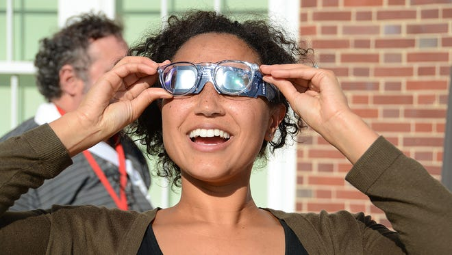 Stacia Mills, a first grade teacher at La Vergne Lake Elementary School, tried on solar eclipse safety glasses provided by Turner Construction to view the late-afternoon sun during a training class outside on the MTSU campus.