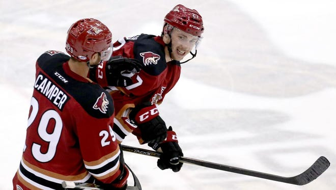 Tucson Roadrunners left wing Carter Camper congratulates Michael Bunting after Bunting's overtime winner on Wednesday.