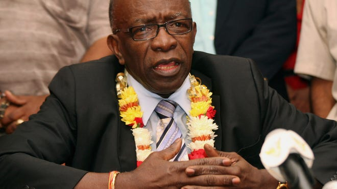 FILE - In this June 2, 2011,  file photo, suspended FIFA executive Jack Warner gestures during a news conference at the airport in Port-of-Spain, Trinidad and Tobago. Interpol added six men with ties to FIFA to its most wanted list on Wednesday, June 3, 2015, issuing an international alert for two former FIFA officials and four executives on charges including racketeering and corruption. Two of the men, former FIFA vice president Jack Warner of Trinidad and former executive committee member Nicolas Leoz of Paraguay, have been arrested in their home counties. Warner has since been released and Leoz is under house arrest.  (AP Photo/Shirley Bahadur, File)
