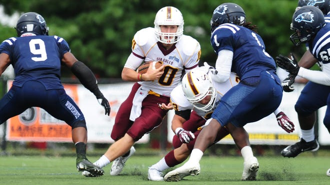 Salisbury University quaterback John Dunbar looks to elude a tackle from Wesley College on Saturday in Dover.