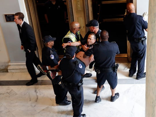 A man is removed from a sit-in outside of Senate Majority Leader Mitch McConnell's office as they protest proposed cuts to Medicaid, Thursday, June 22, 2017 on Capitol Hill in Washington.