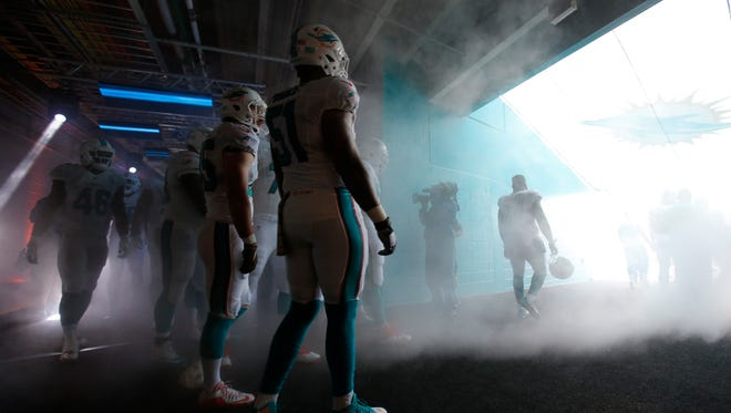 Miami Dolphins come out of the tunnel for team introductions before the start of an NFL football game against the Dallas Cowboys, Sunday, Nov. 22, 2015 in Miami Gardens, Fla. (AP Photo/Wilfredo Lee)