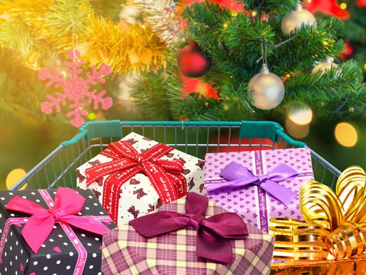 Christmas gifts and presents in shopping trolley cart with christmas tree