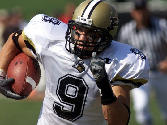 Stuart Schweigert takes off with his first interception against the University of Cincinnati in 2001.