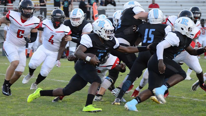 Behind a wall of blockers, Rockledge Raider Jalen Mitchell runs for a first down and more against Palm Bay Pirates at home Friday night.