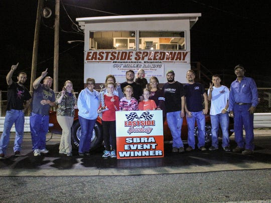 Jamie Brown, top center, poses with family and friends after winning the Footbrake class in drag racing Friday night at Eastside Speedway.