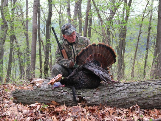 Tim Eisele of Madison poses with a wild turkey he shot
