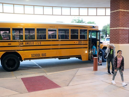 Students arrive by bus at Lamar Elementary on the first