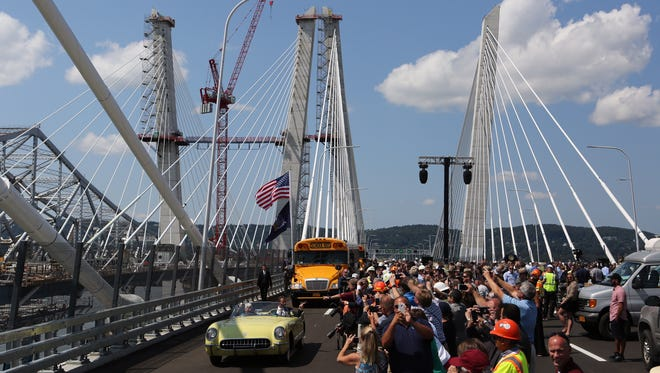 """Onlookers celebrate and take photographs as Gov. Andrew Cuomo, driving a yellow 1955 Corvette with Pearl Harbor survivor Armando """"Chick"""" Galella, leads a procession across the new Tappan Zee Bridge on Thursday during opening ceremonies."""