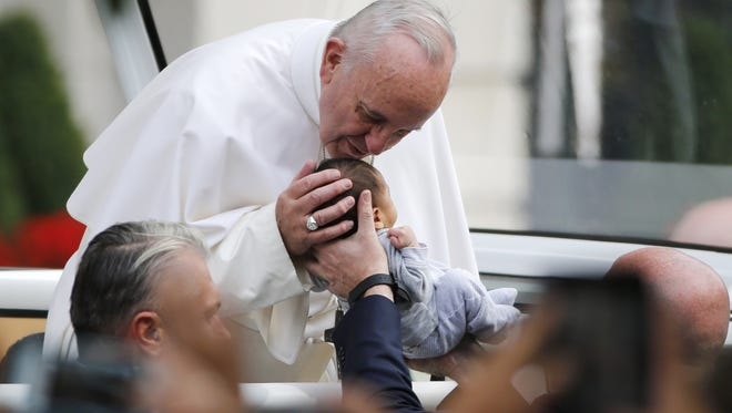 Pope Francis bends over to kiss a small child  at Independence Mall in Philadelphia on Saturday, Sept. 26, 2015.