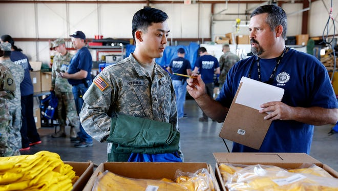 Sgt. Lucas Hoffman (left) selects a wildfire fighting shirt with Mike Brown of the Oregon Department of Public Safety Standards and Training at the Oregon Public Safety Academy in Salem, Oregon, on Thursday, Aug. 31, 2017.
