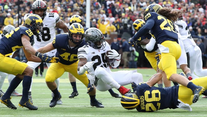 Michigan's Michael Wroblewski and J'Marick Woods tackle Ohio State's Mike Weber in the first quarter Saturday, Nov. 25, 2017 at Michigan Stadium.
