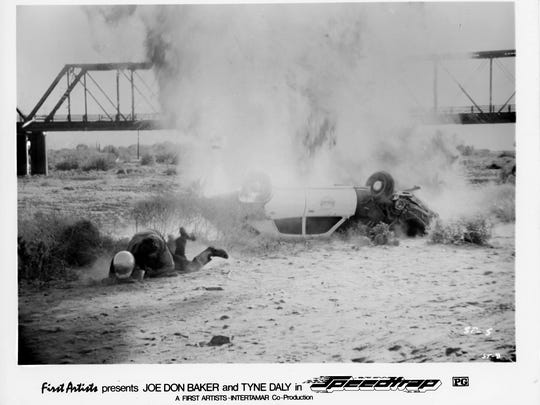 A movie still from the 1977 film Speedtrap shows a Phoenix police cruiser crashed into the Salt River bed after flying off the Ash Avenue Bridge. The 1912 railroad bridge is pictured in the background.