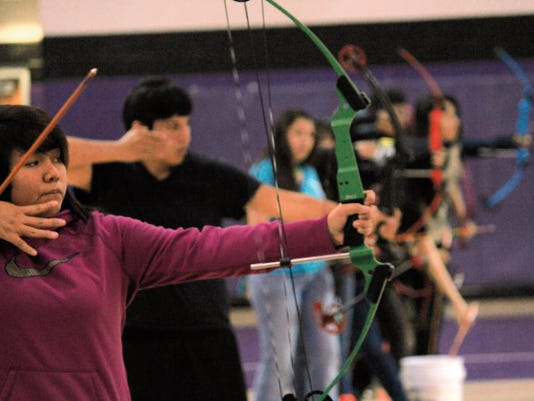 Julie Paz, foreground, practices her archery shooting at the Mescalero Apache School gym Monday afternoon.