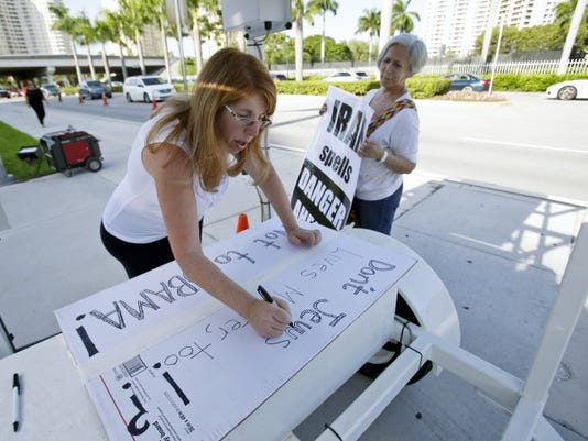 "Caren Besner, center, of Boynton Beach, Fla., draws up a sign that says, ""Don't Jews lives matter, too!? Not to Obama!"" before demonstrating in front of the office of U.S. Rep. Debbie Wasserman Schultz, D-Fla., Monday, Aug. 31, 2015, in Aventura, Fla. About 200 demonstrators gathered to protest against the Iran nuclear deal. (AP Photo/Wilfredo Lee)"